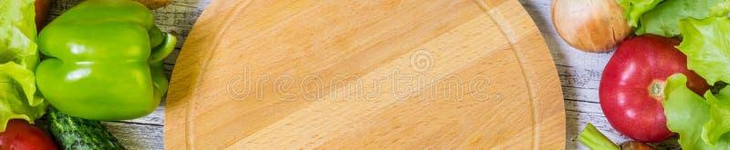 Знамя разделочной доски и овощей круга на белой деревянной предпосылке r стоковая фотография rf