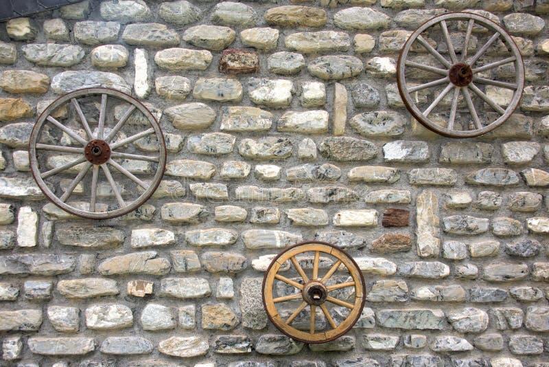 Значительно западное колесо телеги на каменной стене стоковая фотография