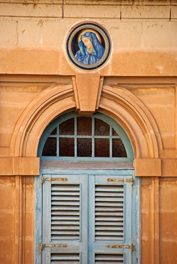 Значок девой марии как украшение на каменной стене дома стоковые изображения