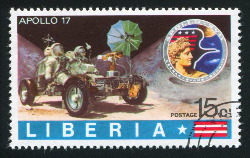 Значок и астронавты Аполлона в кратере луны лунного вездехода исследуя стоковое изображение