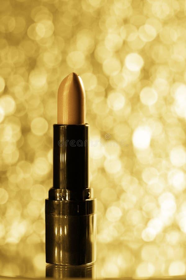 Золотая губная помада на запачканной предпосылке яркого блеска стоковое изображение rf