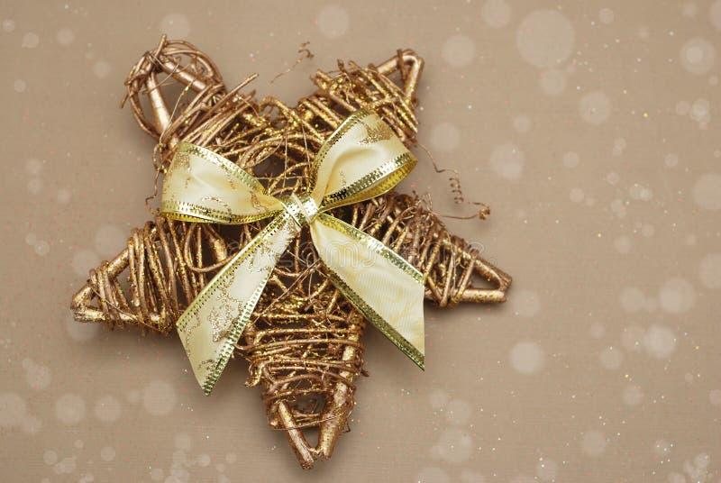 Золотая декоративная звезда рождества с ярким блеском и большим смычком скопируйте космос стоковое изображение