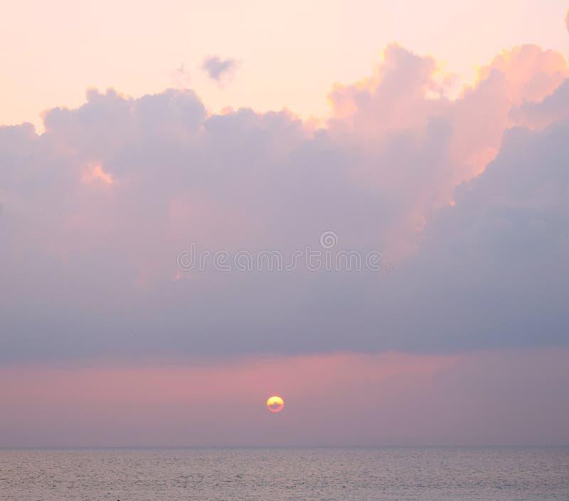 Золотая желтая установка солнца над океаном с темными облаками в ярком розоватом небе - Laxmanpur, острове Нейл, Andaman, Индии стоковое изображение