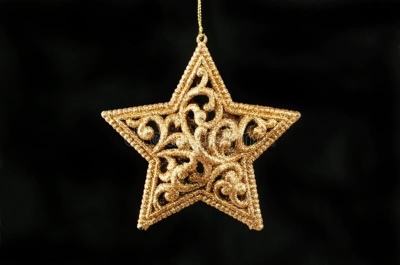 Золотая звезда против черного стоковые изображения