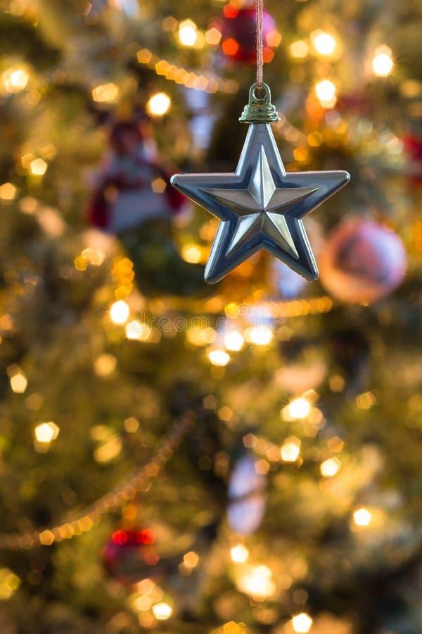 Золотая звезда стоит вне против красочно украшенного рождества в предпосылке стоковые изображения rf