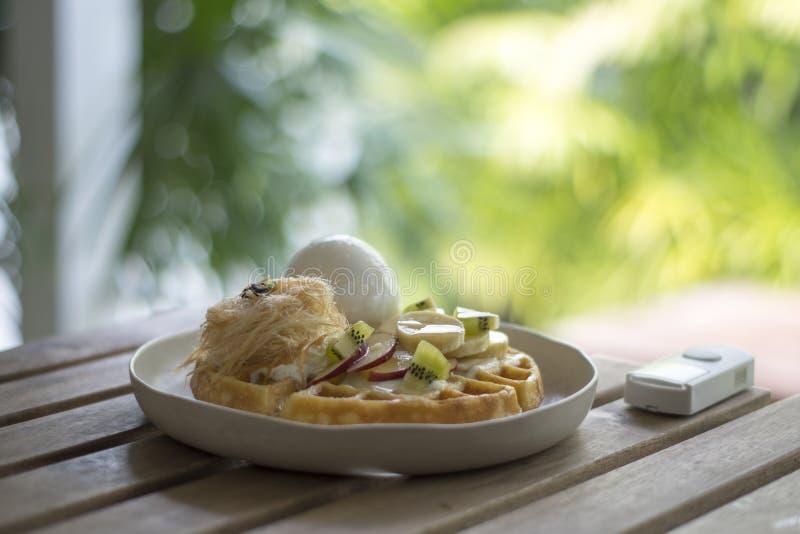 Золотая коричневая вафля покрыла с плодом мороженого стоковое изображение