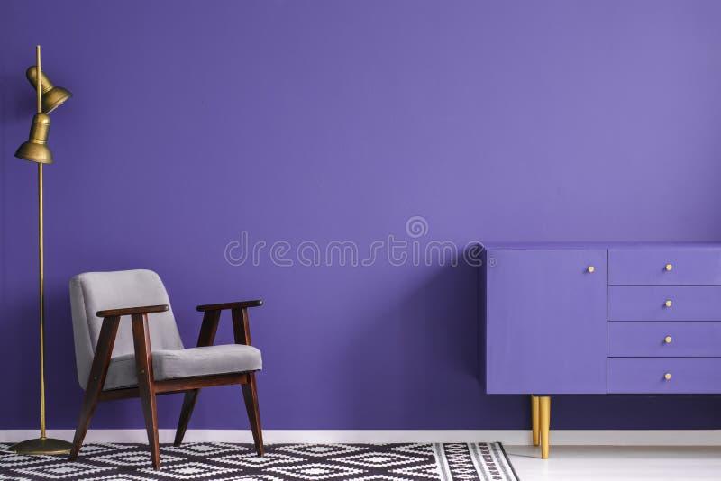 Золотая лампа около серого кресла и ультрафиолетов кухонного шкафа в si стоковое изображение