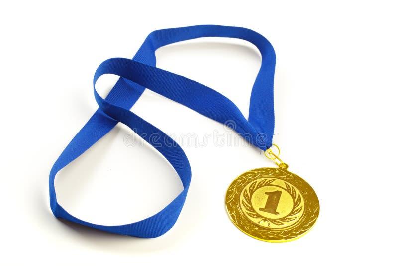 Золотая медаль на переднем плане на голубой ленте стоковые фото