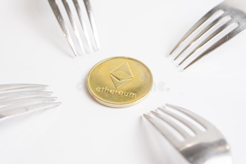 Золотая монета Ethereum cryptocurreny помещенная между вилками на белой предпосылке, трудной вилке стоковые фото