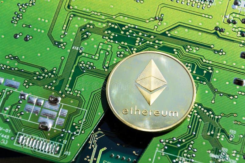 Золотая монетка Ethereum лежа на материнской плате компьютера, cryptocurrency инвестируя, технологии blockchain стоковые изображения