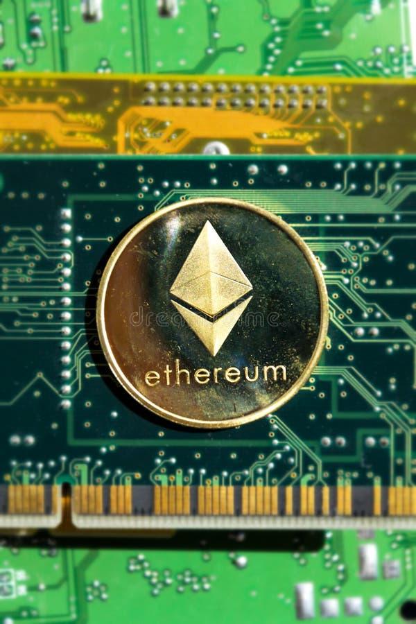 Золотая монетка Ethereum лежа на материнской плате компьютера, cryptocurrency инвестируя, технологии blockchain стоковые изображения rf