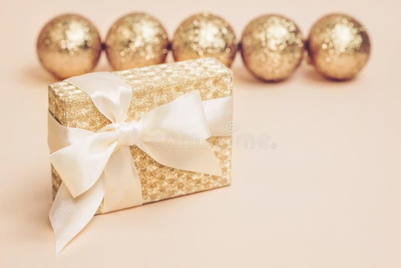 Золотая присутствующая коробка со смычком шелка против шариков рождества золота сверкная на пастельной предпосылке скопируйте кос стоковые фото