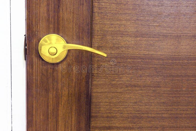 Золотая ручка двери на деревянной двери стоковая фотография