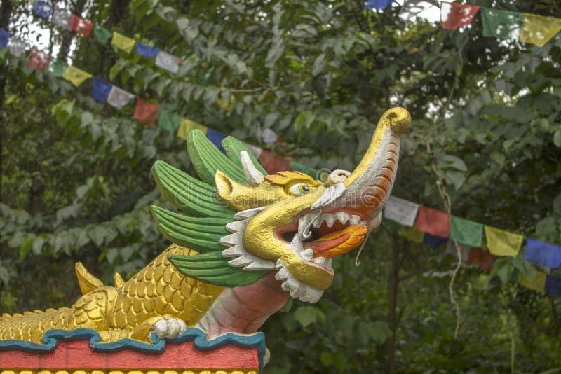 Золотая статуя буддийского тибетского дракона на предпосылке зеленого леса и пестротканых флагов молитве стоковые изображения