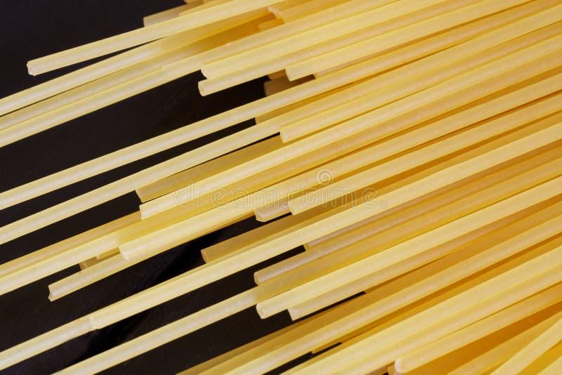 Золотая сырая ложь спагетти на черной деревянной предпосылке minimalism стоковая фотография