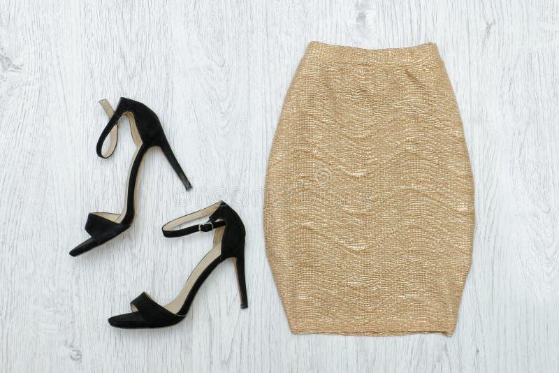 Золотая юбка и черные ботинки модная концепция Деревянное backgr стоковое изображение