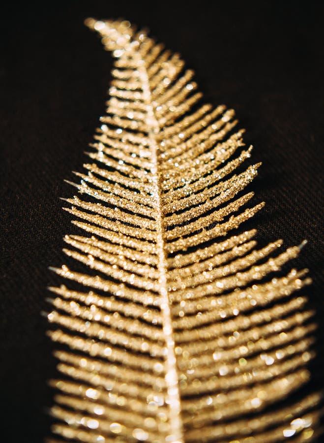 Золотое блестящее украшение лист на темной предпосылке стоковая фотография