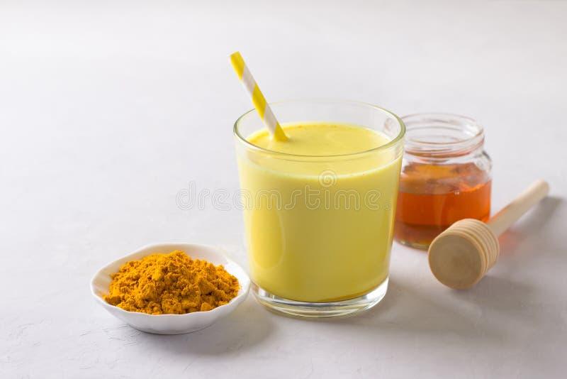 Золотое молоко с турмерином в стекле с медом стоковое фото rf