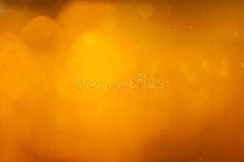 Золотое оранжевое bokeh или роскошный яркий блеск освещают праздничную предпосылку стоковые фото