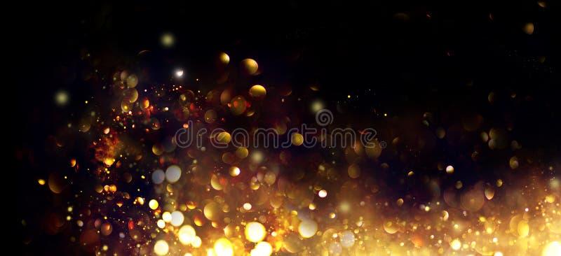 Золотое Рождество и новогодние блестящие звезды вращаются на фоне черного бокаха, на фоне сверкающих золотых звезд стоковая фотография
