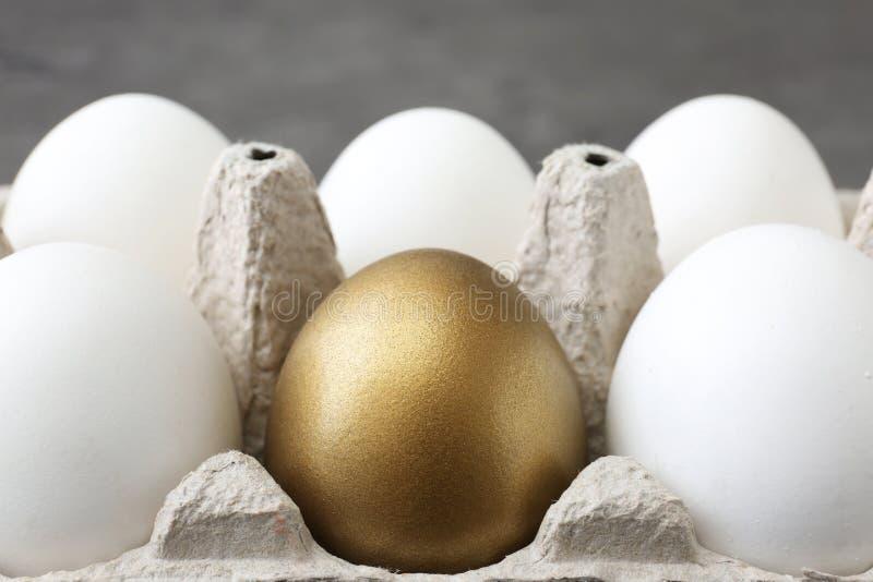 Золотое яйцо и другие в коробке на серой предпосылке стоковые фотографии rf