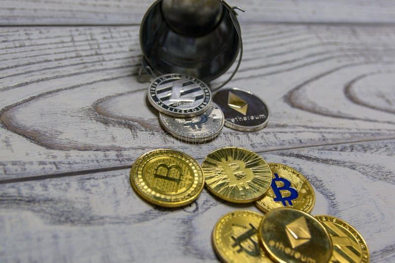 Золотое bitcoin и другая секретная валюта в упаденной игрушке metal крупный план ведра стоковая фотография