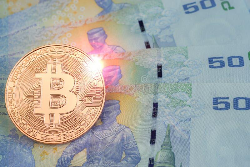 Золотое bitcoin над банкнотой ванны ` s 50 Таиланда, с пирофакелом объектива стоковое изображение