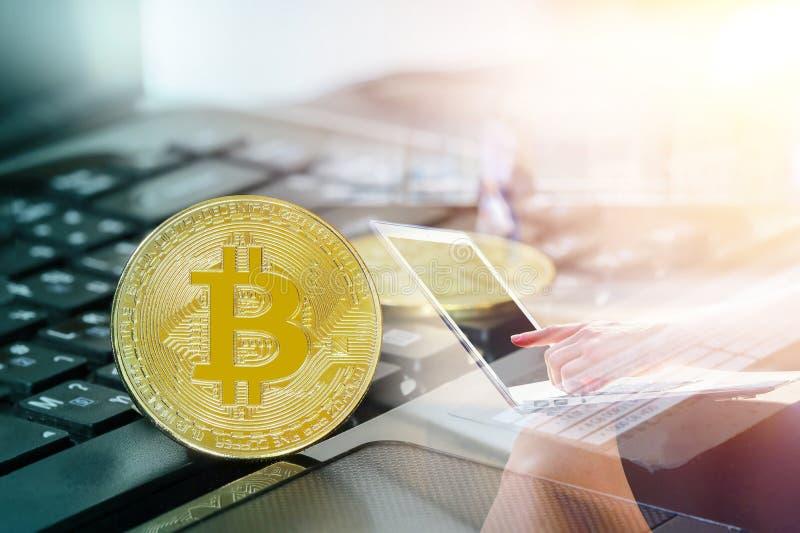 Золотое bitcoin на компьютере клавиатуры с изношенной монетой и по умному телефону стоковая фотография rf
