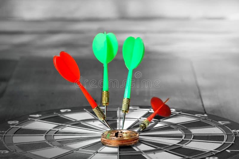 Золотое bitcoin на dartboard с концом вверх по стрелке дротика съемки красной в центре  dartboard стоковая фотография