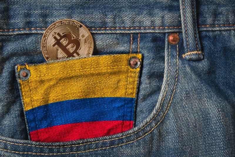 Золотое cryptocurrency BITCOIN в кармане джинсов с флагом республики Колумбии на текстуре джинсов джинсовой ткани стоковая фотография rf