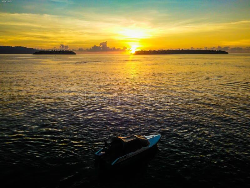 Золотой восход солнца и шлюпка скорости на морской воде штиля на море с предпосылкой 2 островов в Talaud, северном Сулавеси, Индо стоковая фотография rf