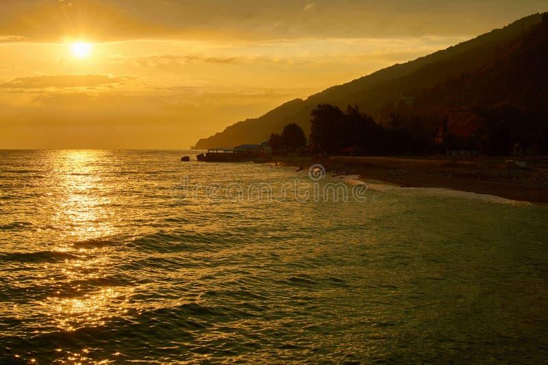 Золотой заход солнца над морем с облаками, гора и пляж внутри освещают контржурным светом стоковые изображения rf