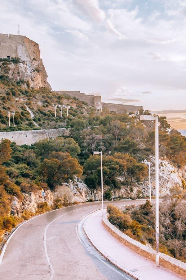 Золотой заход солнца на дороге с замком на заднем плане стоковая фотография