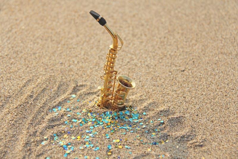 Золотой саксофон альта стоит на песке на фоне голубых shimmers Романтичная музыкальная предпосылка Музыкальная крышка, стоковое изображение rf