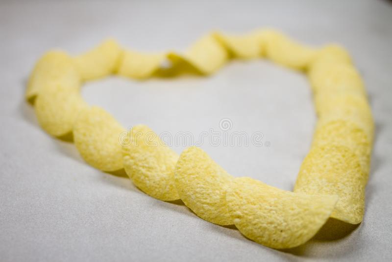 Золотой состав образования сердца картофельных чипсов изолировал над светлым - серая серая белая предпосылка стоковые фотографии rf