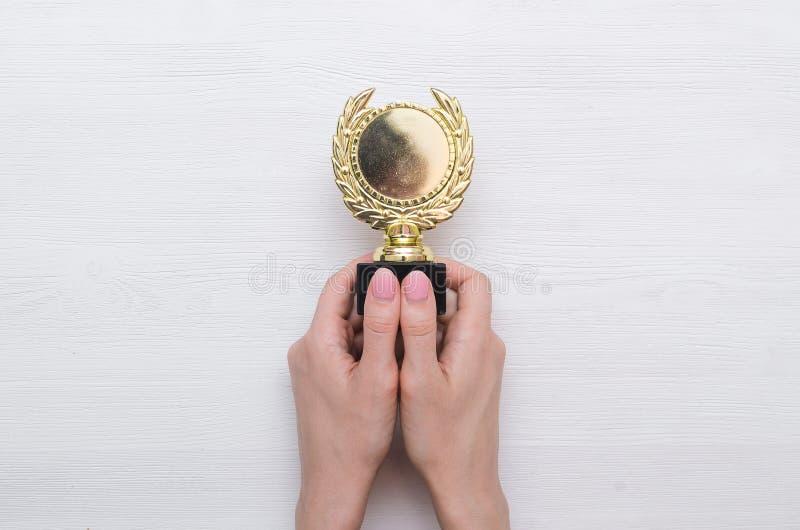 Золотой трофей медали в руке стоковая фотография rf