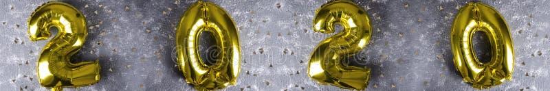 Золотой confetti объявления воздушных шаров на серой поверхности Приветствовать С Новым Годом! 2020 стоковое фото