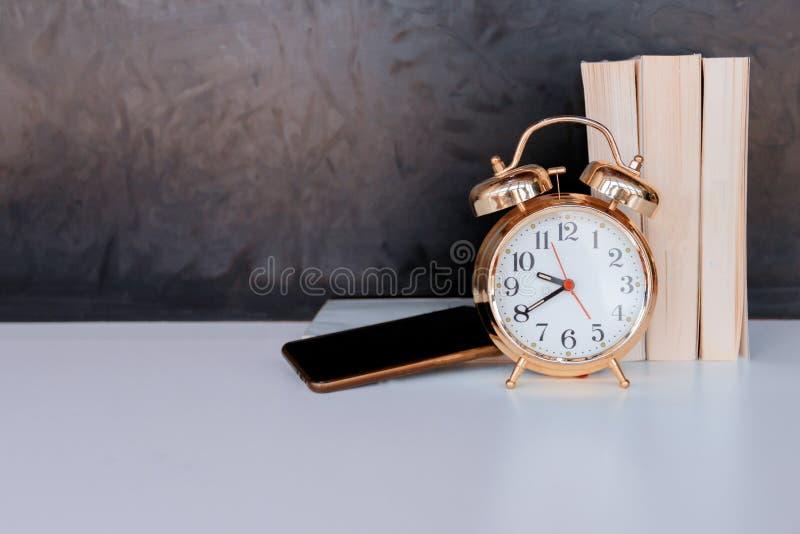 золото будильника старые винтажные и мобильный телефон, книга над белизной на черной предпосылке стоковое изображение rf