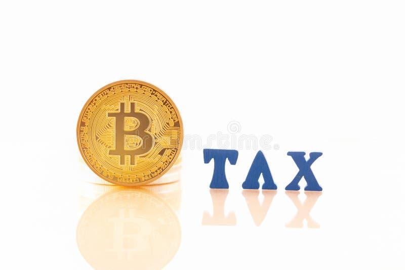 Золото монетки BitcoinBTC и деревянные письма ТАКСИРУЮТ на белой предпосылке стоковые изображения