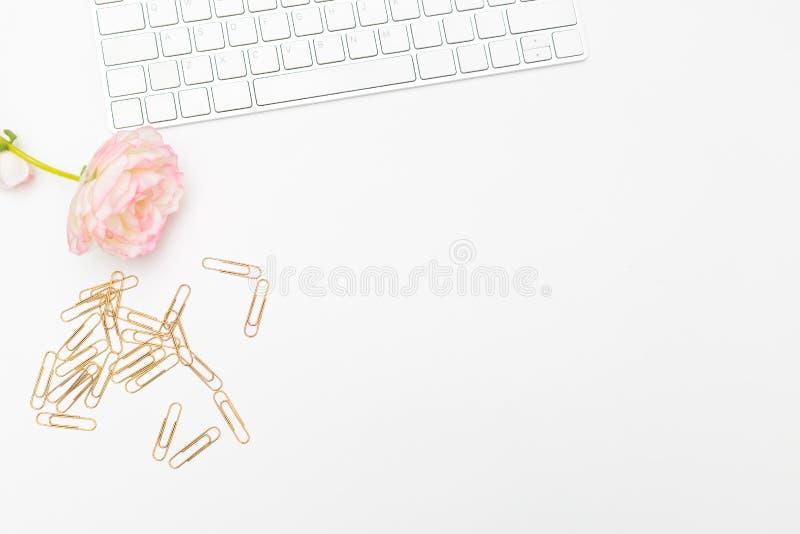 Золотые бумажные зажимы и клавиатура на белой предпосылке офис плоский стоковые изображения