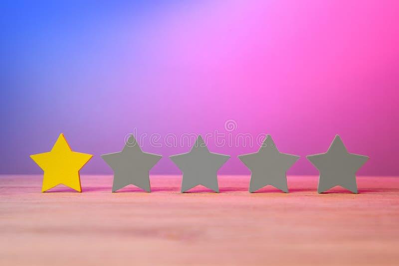 Золотые желтые звезды одно из 5 На таблице звезды, оценка, обзор о фильме Красные фиолетовое и голубой стоковая фотография rf