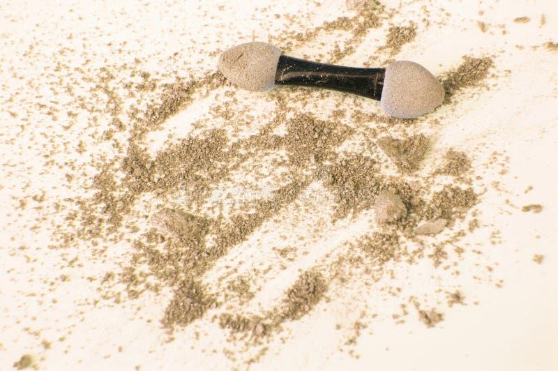 Золотые и бежевые тени для век с аппликатором на белых предпосылке, красоте и концепции макияжа стоковое изображение rf