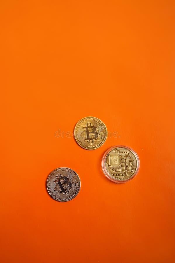 Золотые и серебряные bitcoins вокруг оранжевой предпосылки стоковая фотография