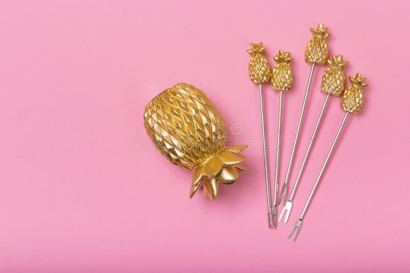 Золотые крышки ананаса на розовой предпосылке стоковая фотография