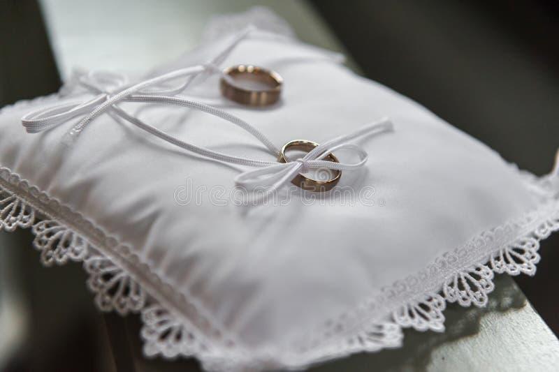 Золотые обручальные кольца на подушке сатинировки в церков стоковые изображения rf