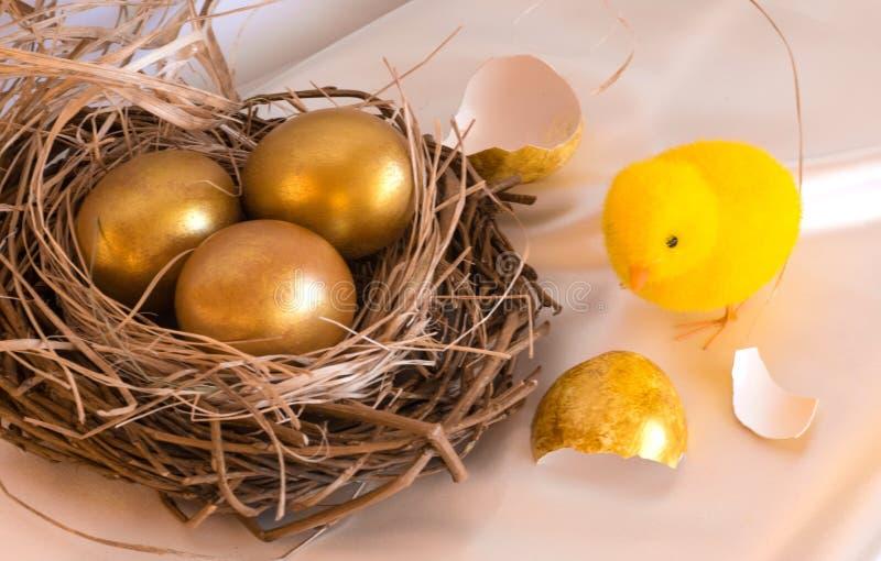 Золотые пасхальные яйца в гнезде и цыпленке ` s птицы стоковое фото