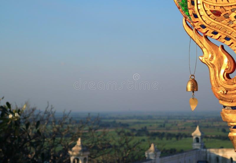 Золотые перезвон ветра и украшение виска Wat Khao Di Salak буддийского с запачканным ландшафтом предгорье в предпосылке, Таиланде стоковые изображения rf