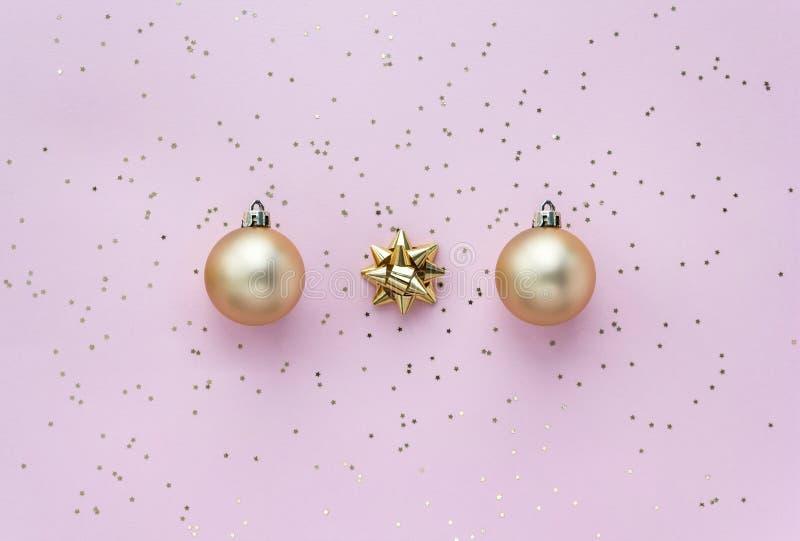 Золотые рождественские мячи, золотые луки и звездные конфетти на розовом пастельном фоне сверху Плоская композиция для праздников стоковая фотография rf