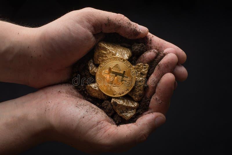 Золотые самородки с bitcoin в руках горнорабочего Минирование идет стоковое изображение