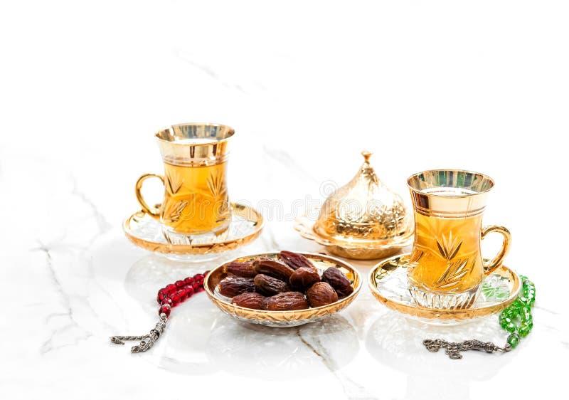 Золотые чашки чая финишировали розовые бусы украшением Рамадана карима стоковое изображение